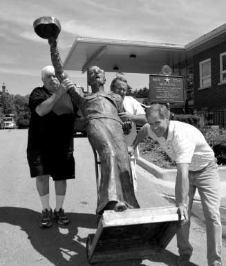 Upon arrival from Michigan, GREG SAGEN (front), MIKE RECHENMACHER, and BOB RECHENMACHER rolled the Spirit of the American Navy sculpture to its temporary home at the Judd Kendall VFW.
