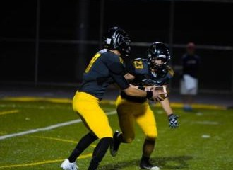 Metea Valley quarterback Conner Lovely hands the ball off to Mitch Webb. Lovely will be aiming to get Metea Valley back to the postseason in 2015 as he steps in for Kyle Mooney.